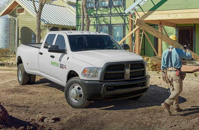 side view of a white 2018 Ram 3500 on a house building site