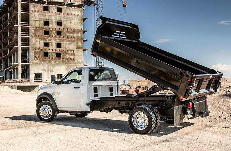white 2018 Ram 5500 Chassis Cab serving as a dump truck on a work site
