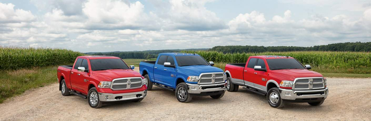 a selection of red and blue 2018 Ram Harvest Edition trucks with a cornfield in the background