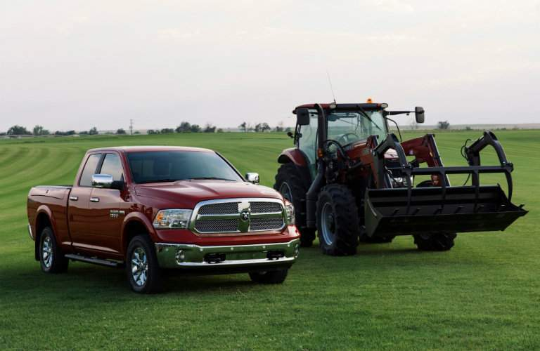 2018 Ram Harvest Edition on a flat field parked next to a piece of farm equipment
