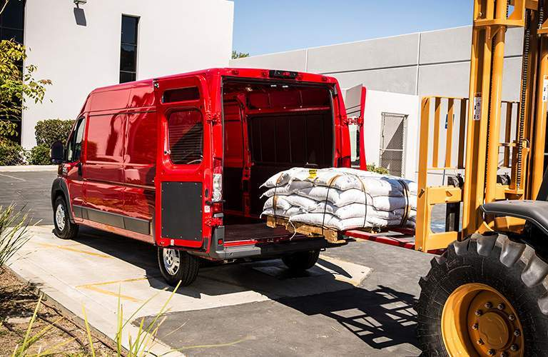 rear view of a red 2018 Ram ProMaster getting loaded by a forklift