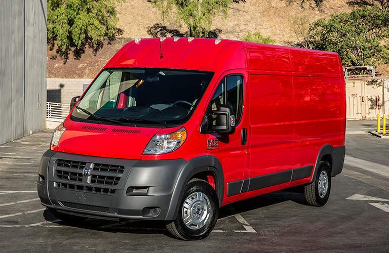 side view of a red 2018 Ram ProMaster in a parking lot with a hill in the background