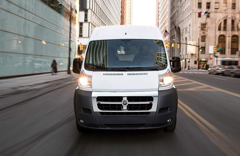 front view of a white 2018 Ram ProMaster driving down a city street