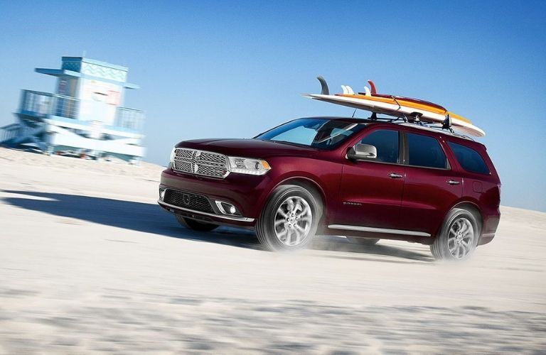 2020 Dodge Durango driving down beach with surfboards