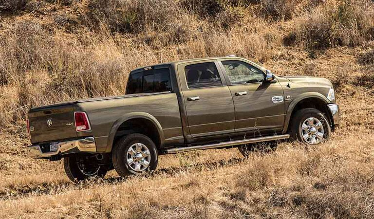 2016 Ram 2500 driving up a hill in a field