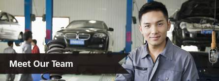 young mechanic smiling at camera in front of cars