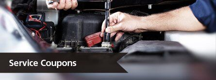 mechanic hands working under hood of car