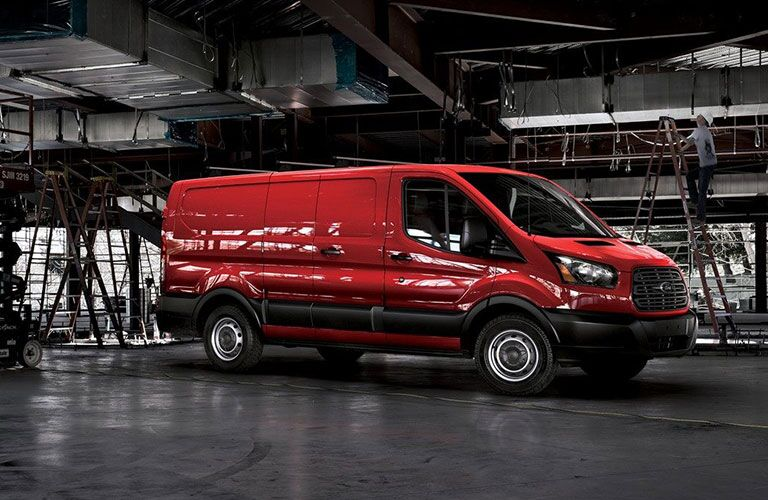 Profile view of red 2019 Ford Transit in warehouse