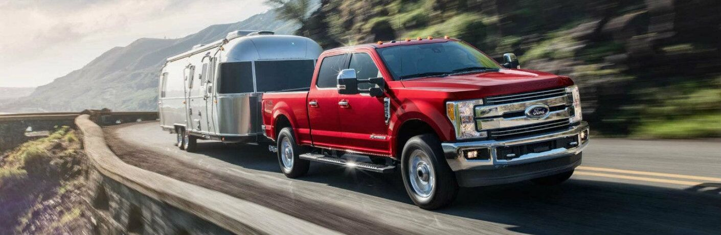 Red 2018 Ford Super Duty F-250 towing trailer on mountainous road