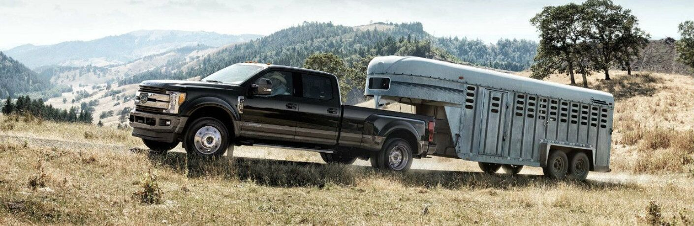 Black 2018 Ford Super Duty F-250 towing trailer on dirt road