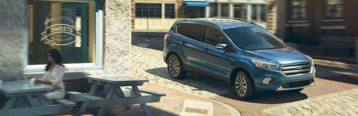Blue 2019 Ford Escape driving on cobblestone city road