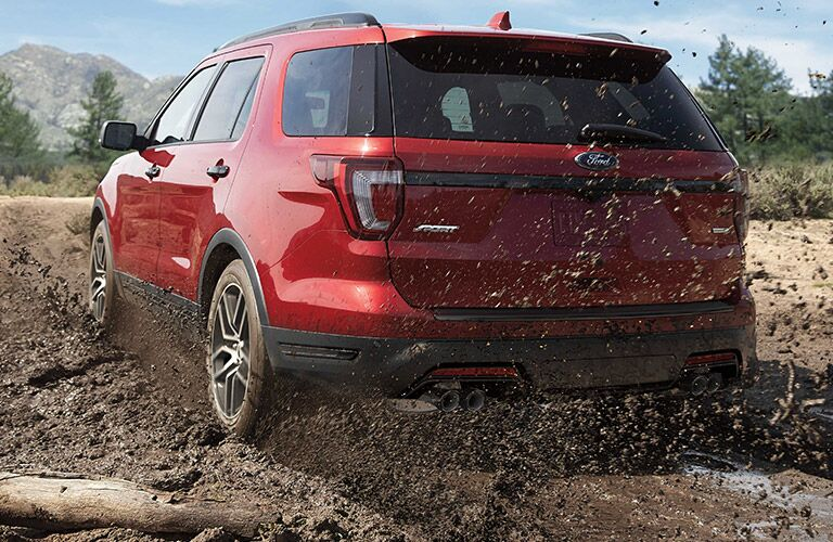 Rear shot of red 2019 Ford Explorer driving through mud