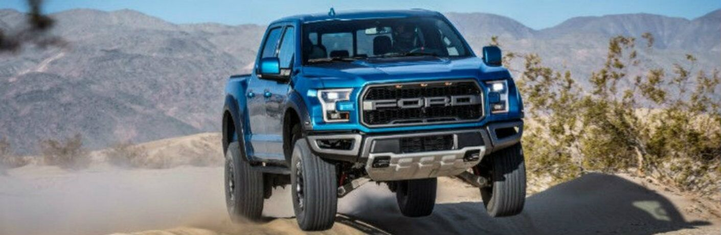 Blue 2018 Ford F-150 Raptor driving over hill in daytime