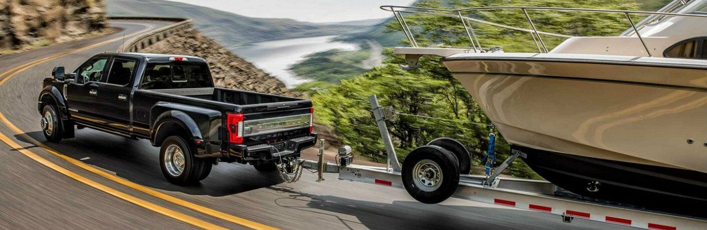 Black 2019 Ford Super Duty F-350 towing boat on winding mountainous road