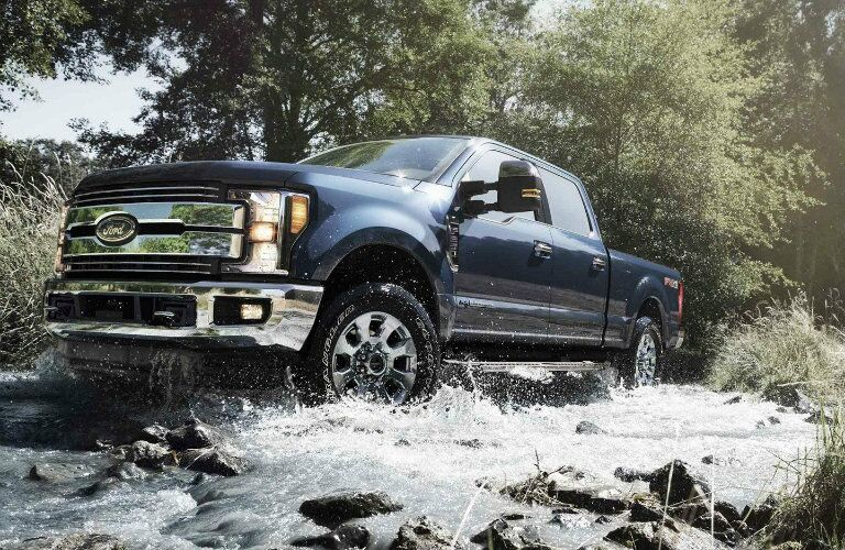 Blue 2019 Ford Super Duty F-350 Lariat driving through water