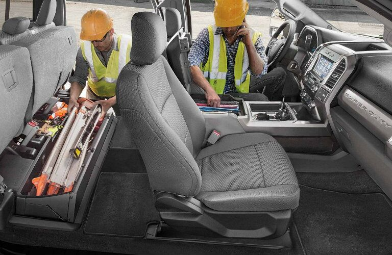 Two workers using cargo management system inside 2019 Ford Super Duty F-350 Platinum