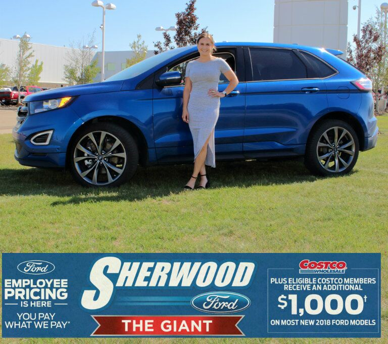 Katherine from Sherwood Ford standing in front of blue 2018 Ford Edge