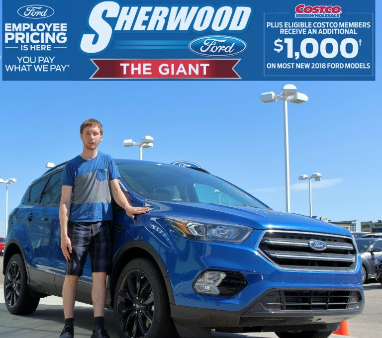 Alex from Sherwood Ford standing in front of blue 2018 Ford Escape