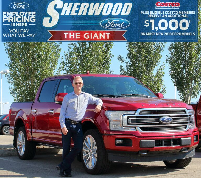 Jerry from Sherwood Ford standing in front of red 2018 Ford F-150