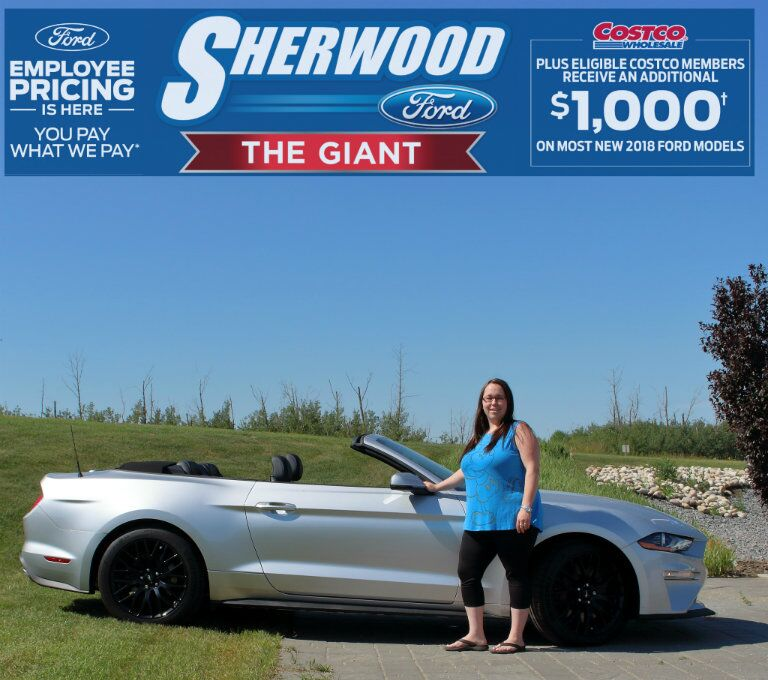 Brandi from Sherwood Ford standing in front of 2018 Ford Mustang convertible