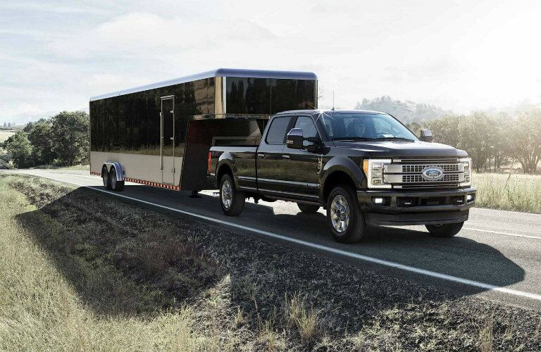 Black 2019 Ford Super Duty F-350 Platinum towing trailer down empty country road