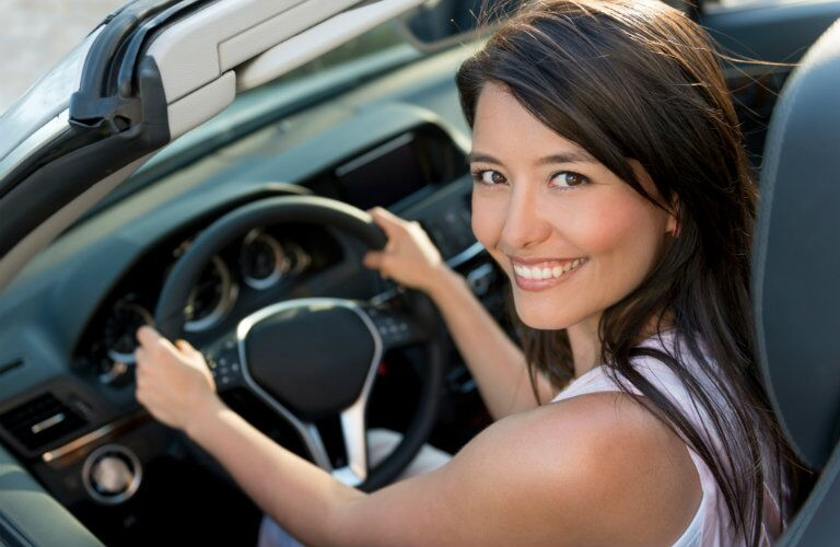 young woman drives home in dream car