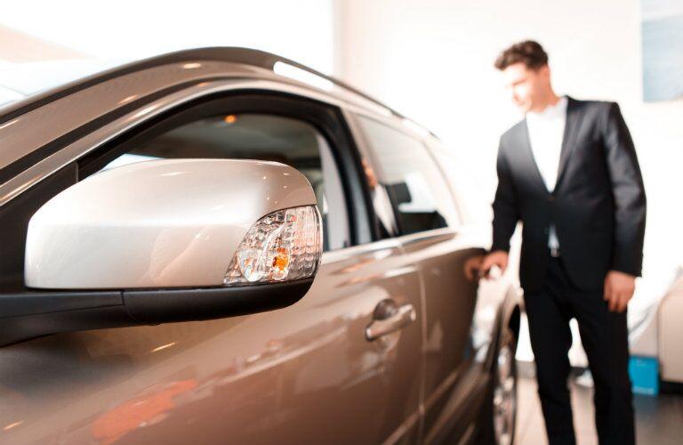 man inspecting car exterior