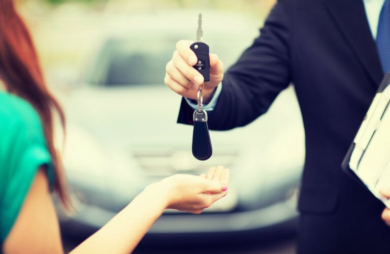 woman receiving keys for new car