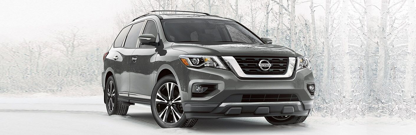 2020 Nissan Pathfinder grey paint shot from front showing grille and passenger doors in front of forest concept background