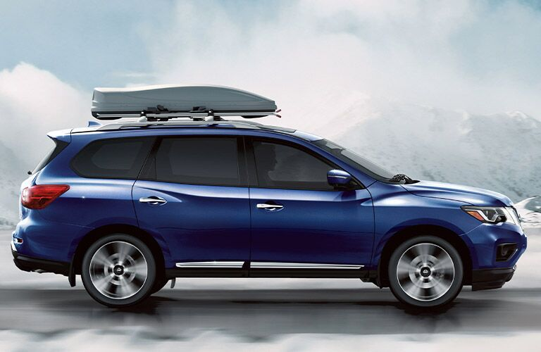 2020 Nissan Pathfinder blue paint facing right exact profile with load mounted to top against concept background