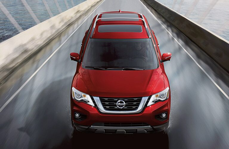 2020 Nissan Pathfinder painted red driving on bridge shot from above showing grille and hood