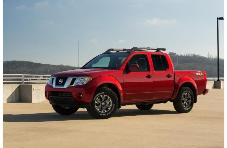 2020 Nissan Frontier red paint parked on parking structure view of driver side
