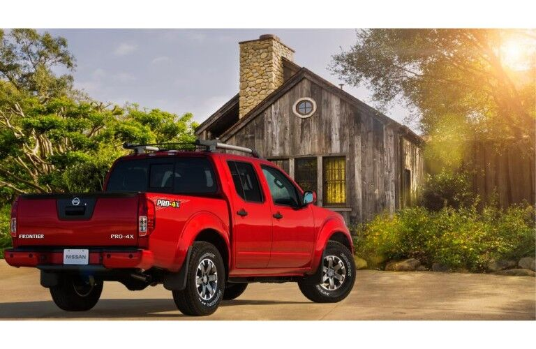 2020 Nissan Frontier red parked in front of old cabin with sun effect