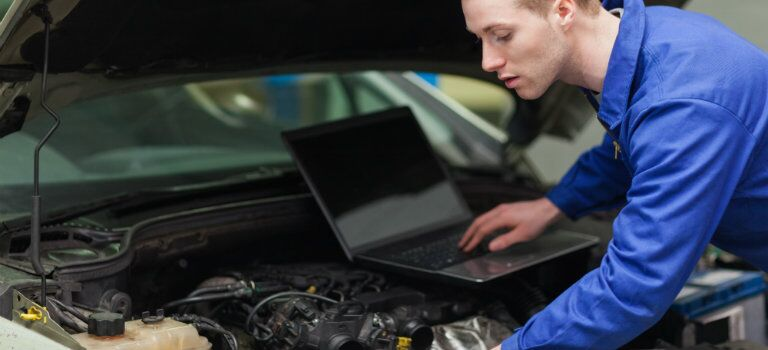 service and repair technician looking under hood of mazda