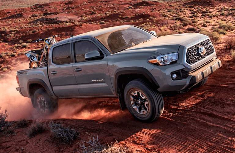 gray toyota tacoma with dirt bike in bed, driving on dirt
