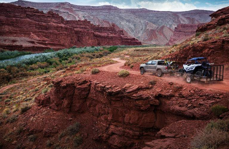 Wide shot of 2018 Toyota Tacoma driving through canyon with ATV in tow