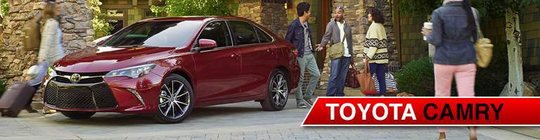 Group of people gathered around red Toyota Camry
