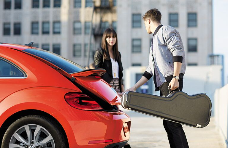 Two people taking music equipment out of the 2016 VW Beetle's trunk