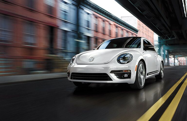 2016 VW Beetle driving under a bridge in the city
