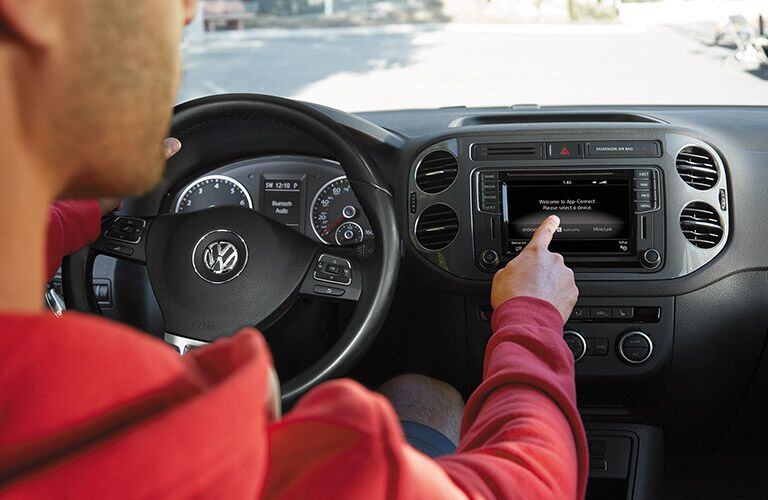 Man in the driver's seat of the 2017 Volkswagen Tiguan using the touchscreen interface