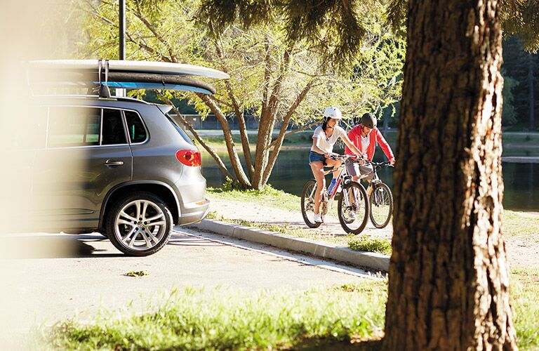 A man and a woman riding bikes near a parked 2017 Volkswagen Tiguan