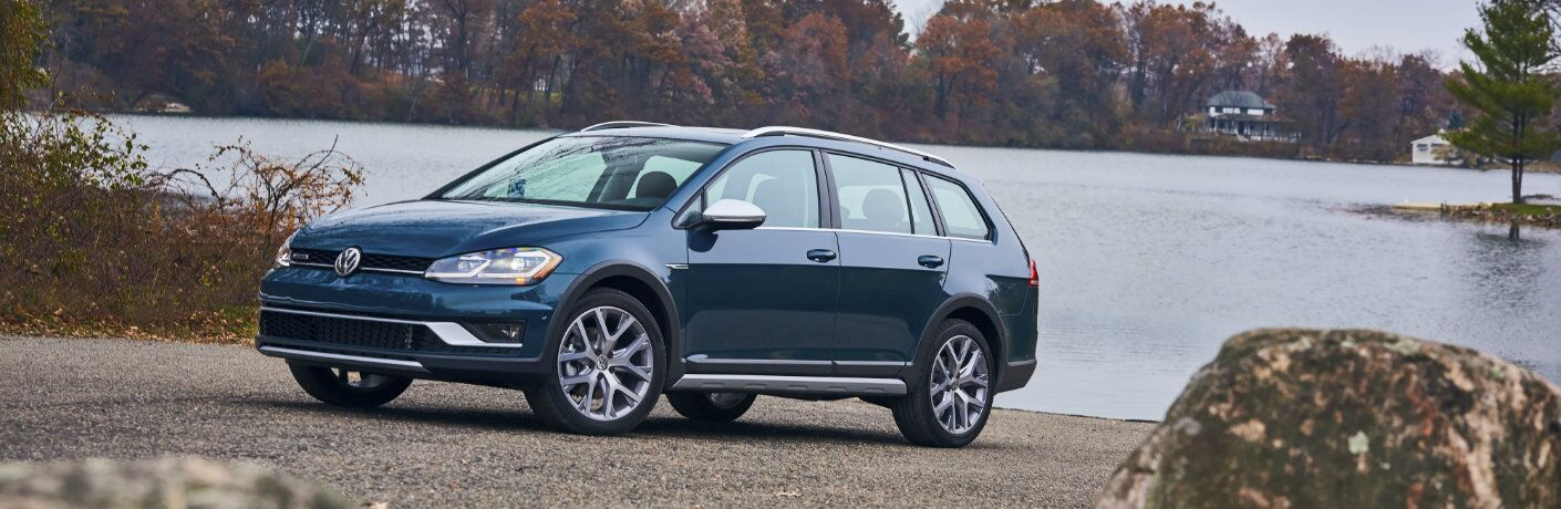 Blue 2018 Volkswagen Golf Alltrack near a lakeside dock
