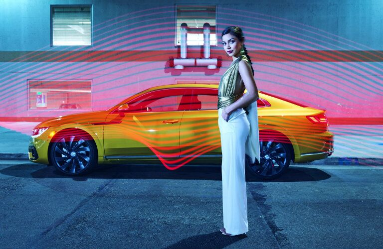 Fashion model standing in front of the side profile of the 2019 VW Arteon photographed by Douglas Sonders