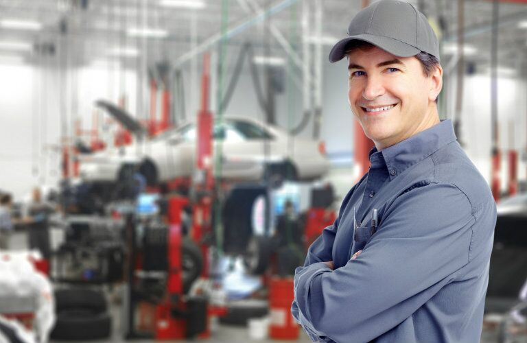 Smiling mechanic with a hoisted vehicle in the background