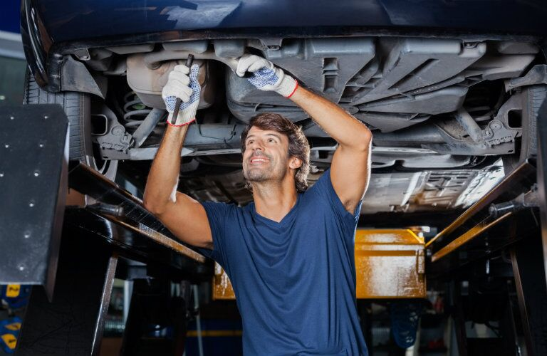 Smiling mechanic making a repair on a hoisted vehicle