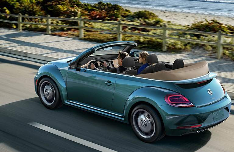 blue 2018 VW Beetle Convertible with the top down driving near the ocean
