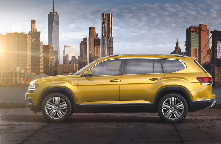 side view of a golden 2018 VW Atlas, city background