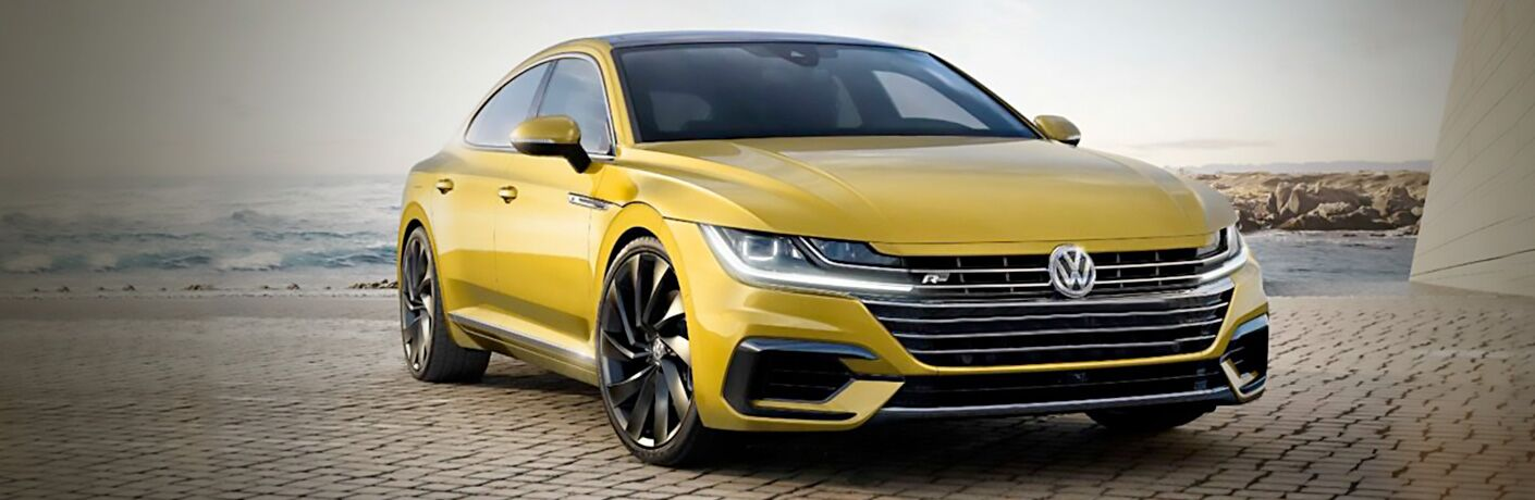 Yellow 2019 Volkswagen Arteon sits happily on a beach.