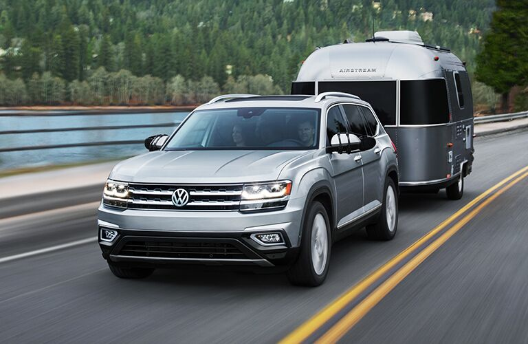 A silver 2019 Volkswagen Atlas tows a camper down a highway by a lake.