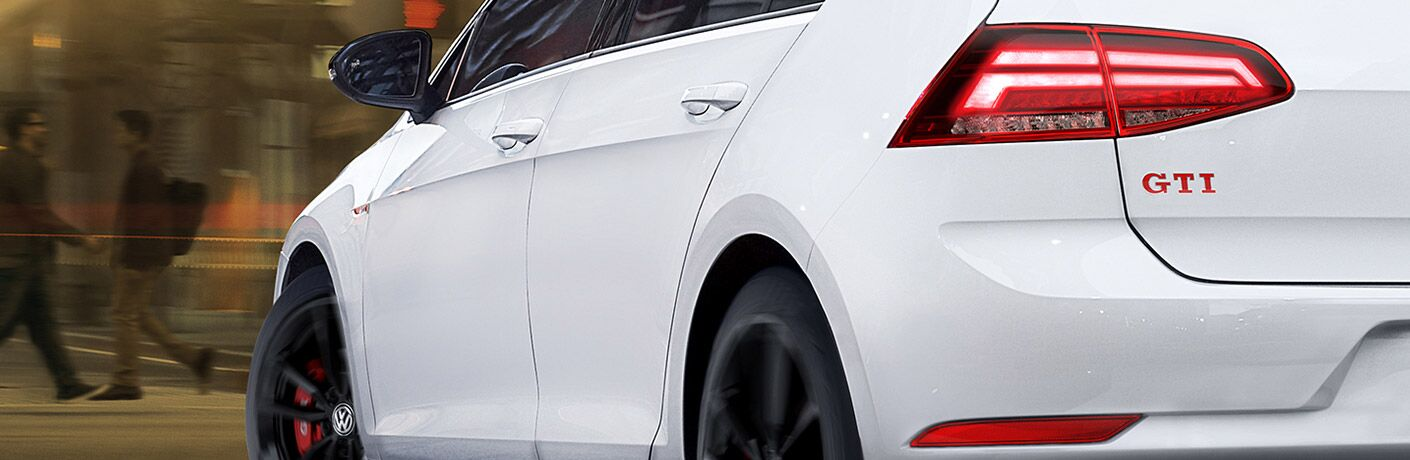 Exterior side and rear of a white 2019 Volkswagen Golf GTI. The GTI letters are emblazoned clearly beneath the left taillight.